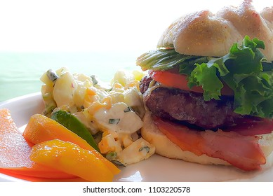 BBQ  bacon cheeseburger with potato salad and fresh fruit
