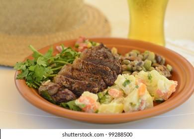 BBQ Beef - Grilled beef served with potato salad, salsa and black eyed pea salad. Churrasco Brasileiro.