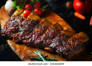 BBQ beef ribs steak served with a hot chili pepper and fresh tomatoes on an old vintage wooden cutting board