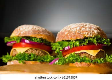 BBQ burger, decorated vegetables and grilled cutlet. Dark background. Home cuisine. Fastfood unhealthy concept. Tradition gourmet food. High calorie food. American table.