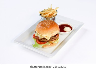 BBQ cheese burger, beef, bacon, onion, cheese, lettuce and sliced tomato served with French fries and mayonnaise, isolated on white background, studio shooting/setup.