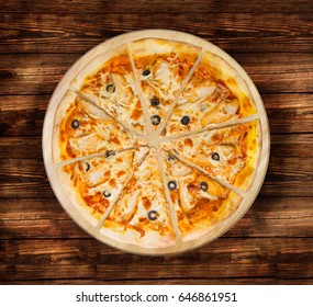 BBQ chicken pizza with olives on the wooden table.  Visit my page. You will be able to find an image for every pizza sold in your cafe or restaurant.