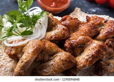 Bbq chicken wings  with red sauce. Closeup