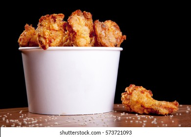 BBQ Chicken wings in a white bucket on a wooden table and black background.