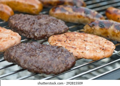 BBQ - Exotic meat burgers and sausages on a lit barbecue (kangaroo, crocodile and wild boar).