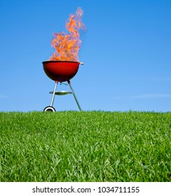 BBQ grill fired up and ready to go. Red charcoal grill against a clear blue summer sky
