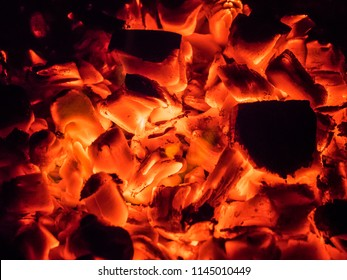 BBQ Grill Pit With Glowing And Flaming Hot Charcoal Briquettes, Food Background Or Texture, Close-Up, Top View, embers, glowing coals, abstract backgroun.
