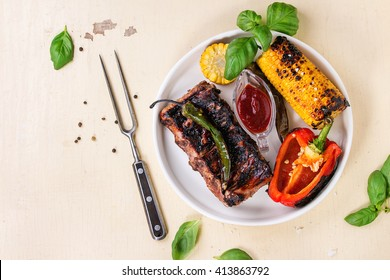 BBQ grilled pork ribs, corn, green chili and red bell pepper, served in white ceramic plate with barbecue sauce, fresh basil and meat fork over white wooden background. Flat lay