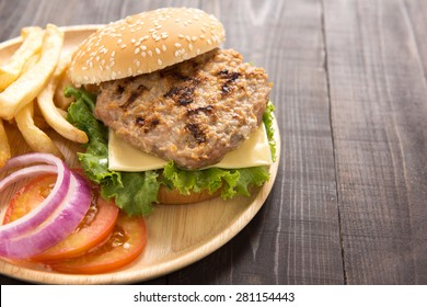 BBQ hamburgers with french fries on wooden background