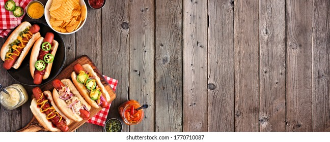 BBQ hot dog corner border. Top view table scene with a dark wood banner background. Copy space.