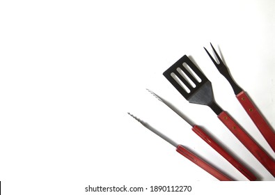 BBQ instruments kit - tongs, spatula, fork - close up isolated on white background flat lay. Image contains copy space