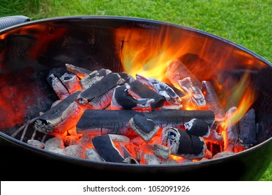 BBQ Kettle Grill With Glowing Hot Charcoal In The Pit. Cookout Food Concept. Outdoor Barbecue Grill With Flaming Coals Ready To Prepare Food On The Backyard Lawn.