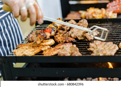 BBQ large grill with roasted meat, stew, sausages, chicken breast. Low angle perspective. Horizontal crop