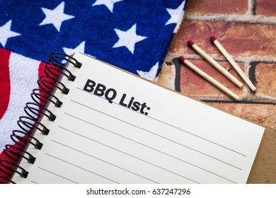 BBQ List concept on notebook and brick background with stars and stripes banner and matches