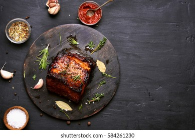 Bbq meat, grilled pork on dark background with copy space.