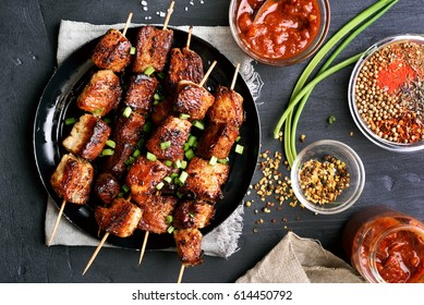 Bbq meat on wooden skewers on plate. Top view, flat lay