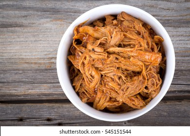 bbq pulled pork bowl over a wooden plank table