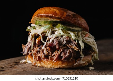 BBQ Pulled Pork Sandwich with coleslaw and dill pickles on horizontal dark background