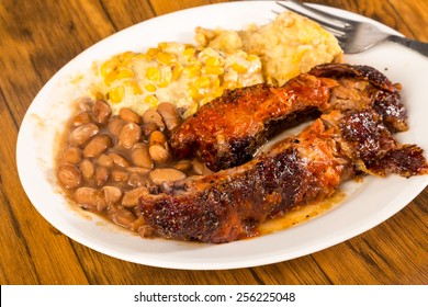 BBQ rib plate with jalapeno corn and borracho beans and tater tot casserole on rustic wooden boards.