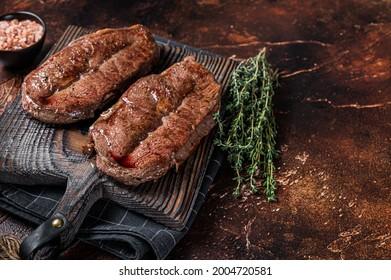 BBQ roasted Shoulder Top Blade cut or Australia wagyu oyster blade beef steak. Dark background. Top View. Copy space