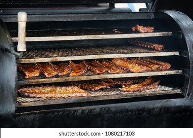 bbq spareribs in barbecue smoker, grilled pork meat ribs