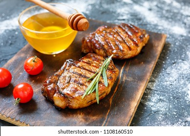bbq, Steak barbecue with ketchup with rosemary, honey closeup. Grilled beefsteaks on cutting board - dinner preparation. copy space, selective focus,