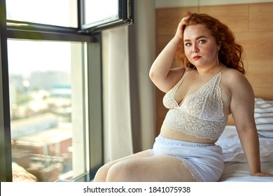 BBW big beautiful caucasian woman showing off overweight figure wearing sexy lingerie, sitting on bed, posing, having rest