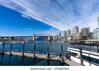 BC, Canada - MAR 05 2021 : Granville Island Ferry Dock. Burrard Street Bridge and Vancouver buildings skyline in the background.