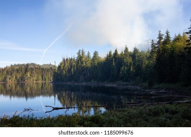 BC Wild Forest Fire near a lake during a hot summer day. Located near Port Alice, Northern Vancouver Island, BC, Canada.