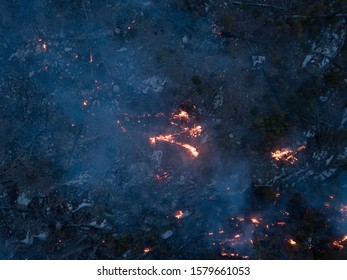 BC Wildfire burning and flames in overhead drone shot. Aerial view onto forest fire at twilight or dawn. Flames, glow, blaze and smoke over dead woods and trees.
