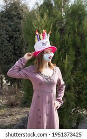 b-day celebration during self isolation. birthday woman in a medical mask with painted lips, in funny hat in form of cake with candles. humor concept, thinking positively in covid-19 pandemic