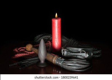 bdsm background red wax candle with fire and leather whip with rope for tying