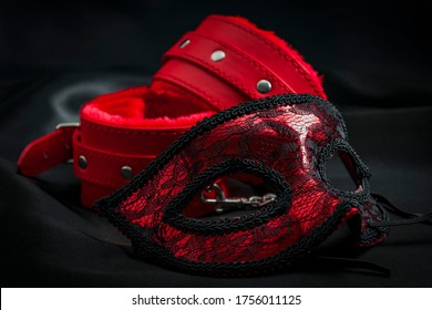 BDSM, bondage play, fetish wear and kinky sex toy concept with close up on erotic mask and red handcuffs isolated on black silk background