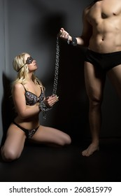 BDSM concept. Beautiful submissive tied with chain