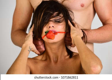 BDSM concept. guy puts the strawberry in girl's mouth. Gag closeup. Sexy couple play in love games