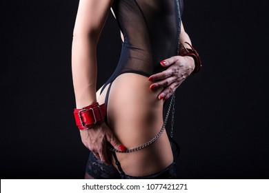 BDSM Concepts. Side View of Mature Caucasian Female Posing with  Accessories for Sado-Masochism Play. Tied with Chain and Wristbands. Against Black. Horizontal Image Composition