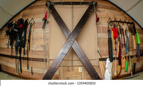 BDSM dungeon Saint Andrews's cross and impact play gear wall
