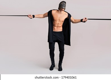bdsm man with leather mask on grey background