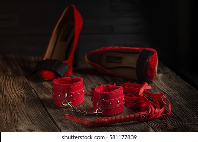 BDSM red handcuffs, scourge and lingerie on a black background, bondage element to immobilize partner. Sex shop stuff.