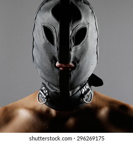 Bdsm style image with a men wearing a leather mask or hood over his head
