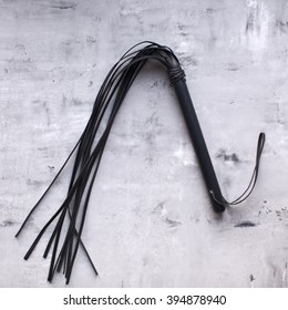 Bdsm whip against concrete wall