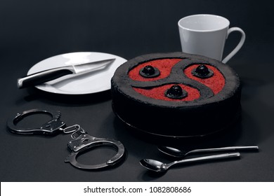 BDSM-themed cake with a white plate, a white cup, kitchen utensils and handcuffs, on dark background