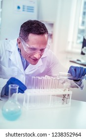 Be attentive. Kind brunette man keeping smile on his face while staring at test tubes