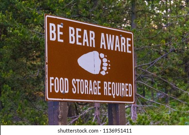 Be Bear Aware warning sign posted in hiking and camping area for safety against a black bear or grizzly bear attack