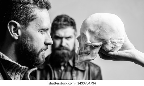 Be brave. Focused on breaking fear. Psychology concept. Human fears and courage. Looking deep into eyes of your fear. Man brutal bearded hipster looking at skull symbol of death. Overcome your fears.