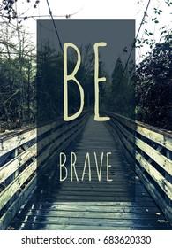 Be Brave typography design on image of long wooden walking bridge.
