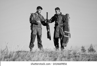 Be careful. Hunters gamekeepers walk mountains background. Hunters with rifles in nature environment. Hunter friend enjoy leisure in field. Hunting with friends hobby leisure. Safety rules concept.