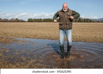 To be a child again. Funny old man jumps with rubber boots through the puddle on the meadow.