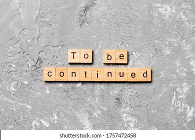 To be continued word written on wood block. To be continued text on cement table for your desing, concept.