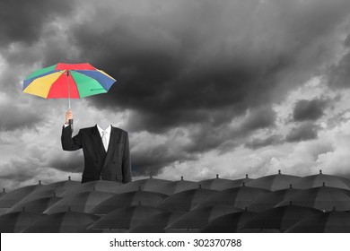 Be a different businessman concept , man holding rainbow umbrella in mass of black umbrellas with dark sky